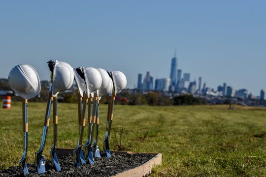 Hard hats on shovels with Manhattan skyline in the distance